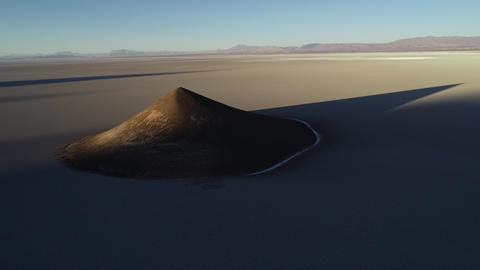 Aerial general view of natural isolated pyamid in wide brown and white salar at sunset. Flying Footage