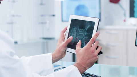 Doctor looking and analyzing X ray on a digital tablet pc... Stock Video Footage