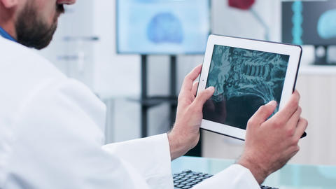 Doctor looking and analyzing X ray on a digital tablet pc screen Footage
