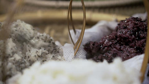 Steaming 3 colors stick rice, white, purple and sesame mixed in Thai market Live Action