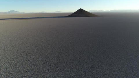 Aerial scene flying towards natural pyramid at white and salar, general view of impressive cone. Footage