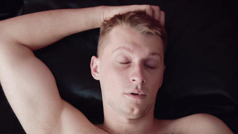 Man wakes up in bed early in the morning Live Action
