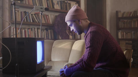Young man in sweater is sitting on stool in front of retro TV in furnished room Footage