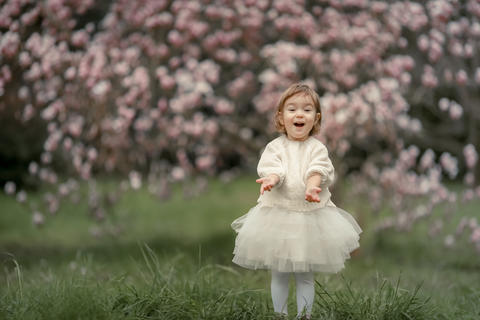 Portrait of happy joyful child in white clothes over tree flowers blossom Photo