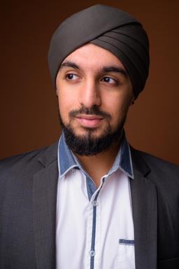 Young bearded Indian Sikh businessman wearing turban against bro Photo