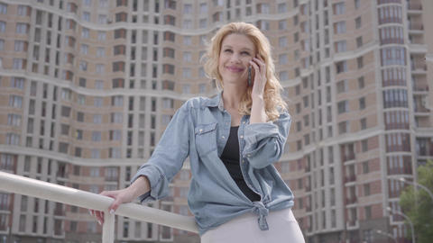 Confident smiling blond woman in jeans jacket talking by cellphone in front of Live Action