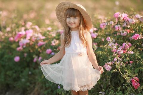 Little girl in a white dress in a broken hat on a lavender field Photo
