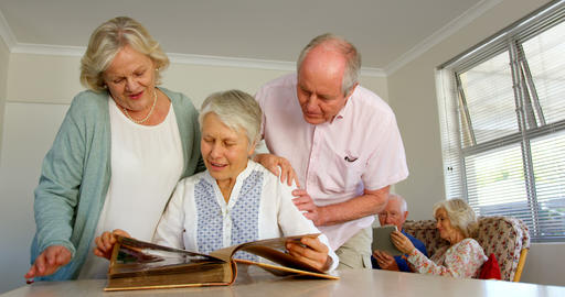 Front view of active Caucasian senior people looking at photo album in nursing home 4k Live Action