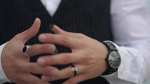 Crossed fingers close up of stylish man on the classical suit. Stylish watch on Live Action