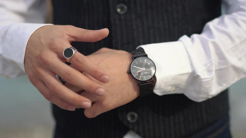 Businessman in classical suit looking at his watch on his hand, watching the Live Action