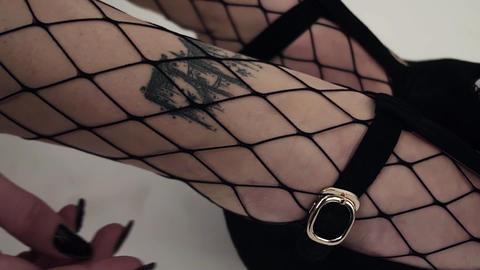 Close-up of female's legs in black checkered stockings in black shoes Live Action