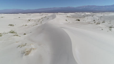 Aerial drone scene of detail of dunes and sand desert with plants and the andes mountains on Footage