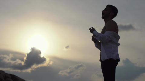 Young man in sunset take off his white classical shirt and happily enjoying Footage