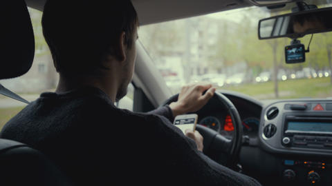 young man using map app on his smartphone in a car. Footage young man behind the Live Action