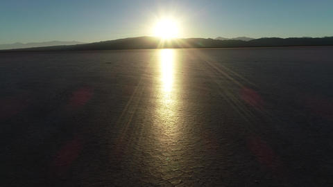 Aerial drone scene flying towards the horizon at sunset in dry shinny broken soil. Sun reflects over Footage