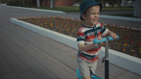 Happy little boy two years old, riding a scooter in a summer park Footage