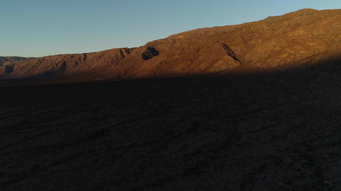 Aerial drone scene, flying fowards, general view of dry arid mountain belt at golden hour. Footage