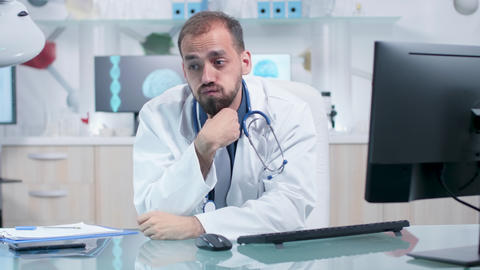 Tired and exhausted physician in his office working Live Action