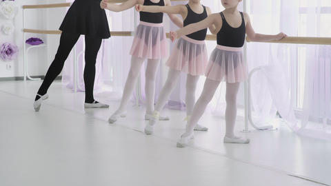 Small ballerinas are repeating the movements with the teacher. ballet lesson in Footage