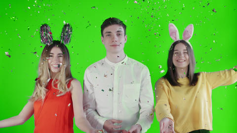 Two beautiful girls throw confetti and young man Exploding party popper on green Live Action