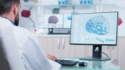 Over the shoulder shot of doctor in research facility looking at 3D brain scan Live Action