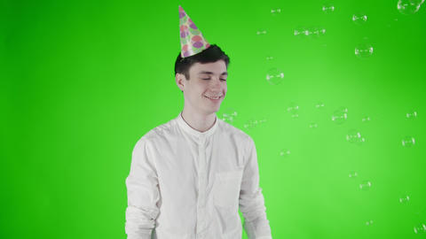 Young man with party hat is surprised flying bubbles on a green screen Footage