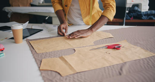Designer outlining piece of material with tailor's chalk making handmade clothes Live Action