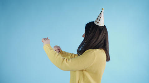 Young woman in yellow sweater with party hat is dancing on a blue background Footage