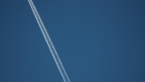Commercial airplane passing over leaving contrails behind Live Action