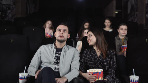 Positive couple are eating popcorn and discussing a movie Footage