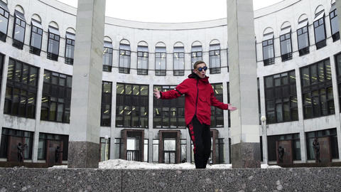 Cool guy in red sport outfit and sunglasses raps next to granite columns Footage