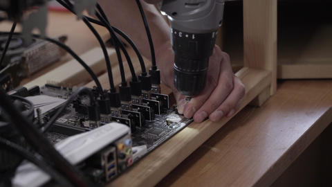 Man's hands use electronic screw driver to connect motherboard to wooden plank Live Action