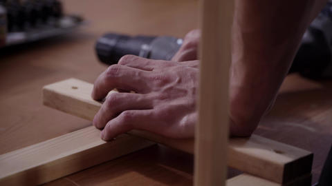Man's hands are working with modern electronic screw driver to connect planks Footage