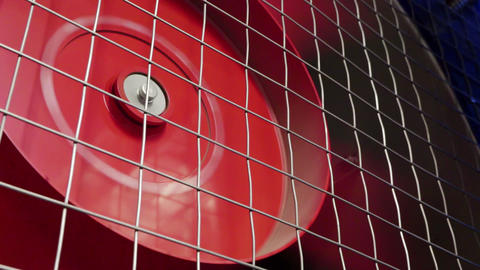 Huge rotating red cooler is intensively working behind thin grey grille Footage