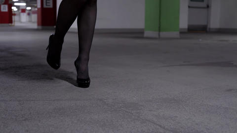 View of walking female's legs in black stockings and high heels in garage Live Action