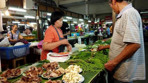 Lampang, Thailand - 2019-03-07 - Market Vendor Makes a Sale of Greens Footage