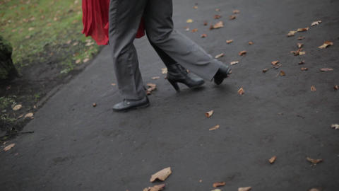 Woman's legs in red skirt and man's legs in grey pants dance tango in autumn Live Action