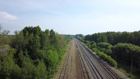 Summer scenery of empty long railways laying along green line of forest trees Footage