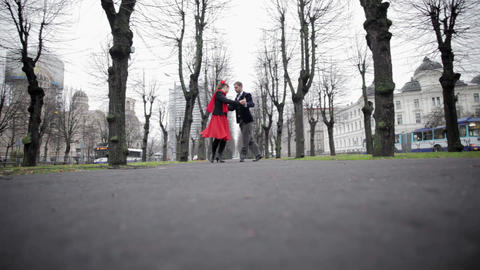 Young couple dances tango in cold empty winter park surrounded by naked trees Footage