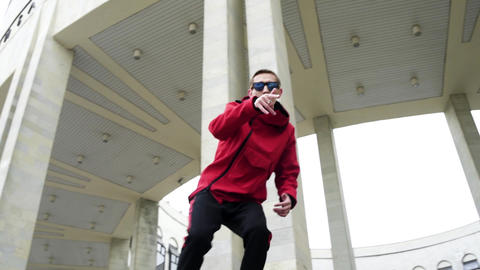Cool young man wearing red jacket and sunglasses emotionally rapping Footage