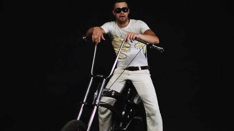 Guy with sunglasses sits on bicycle, holds handle grips and turns handlebars Footage