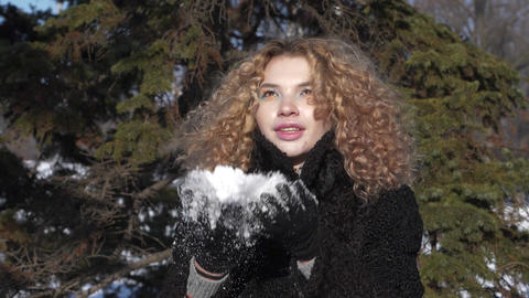 A young woman with a curly haircut in a black coat throws snow over herself Footage