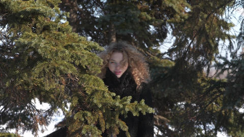 Suddenly, the snow flies to the girl's face Curly girl in a black coat on a Footage