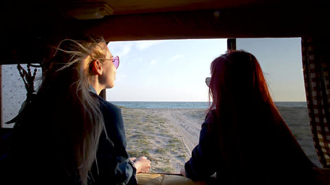 Couple of young women look to the sandy beach and sea thru the auto trailer Footage