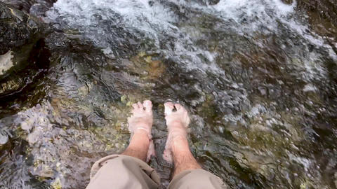 Man putting his bare feet in a cold water in a mountain stream or river in slow motion Footage