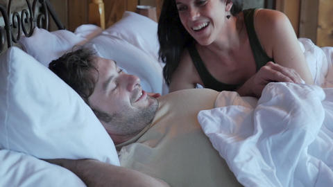Happy couple lying in bed together waking up and starting their day talking to each other in slow Footage
