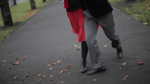 Woman's legs in red skirt and man's legs in grey pants dance tango in park area Live Action