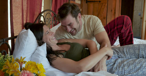Fun loving happy couple laughing and being affectionate in bed during the day on a casual morning Footage