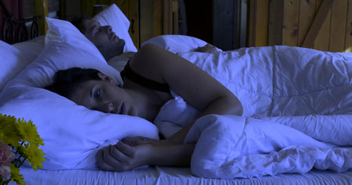 Woman tossing and turning in bed because she can't sleep next to a man who turns over in her bed at Footage