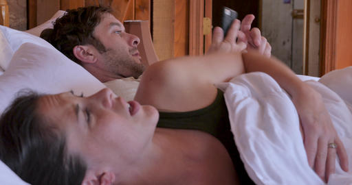Phone call wakes up a young attractive couple in the morning as the man answers the smart phone in Live Action